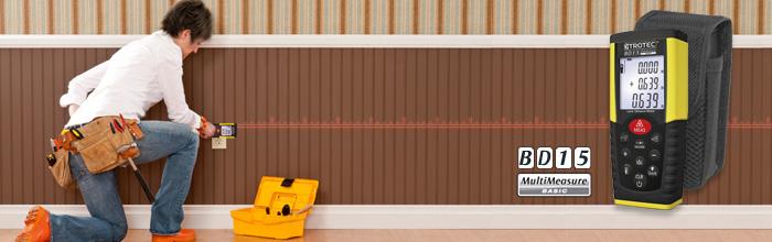 Una mujer mediendo la largura de la pared con el telémetro a distancia